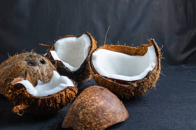 Coconut cut in half on a black background