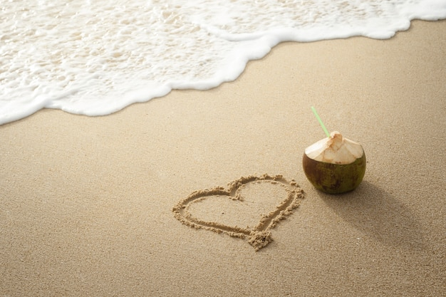 Coconut drink and drawn heart on the sand