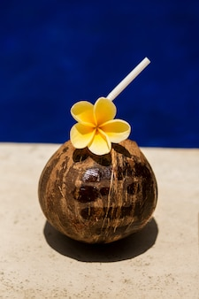 Coconut drink with yellow flower at poolside