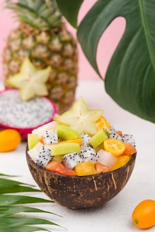Coconut filled with fruit salad and monstera leaf