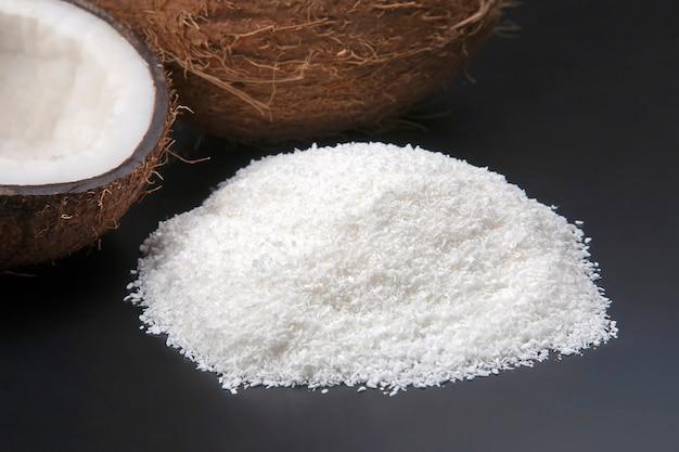 Кокосовая стружка на темной поверхности рядом с кокосом. витаминные фрукты. здоровая пища