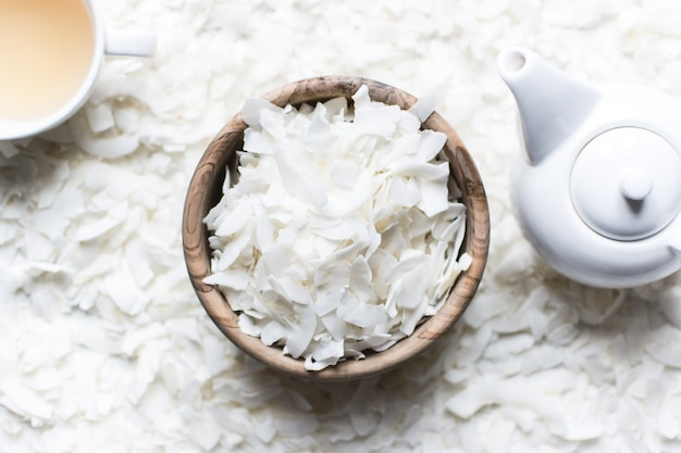 Coconut flakes with tea and teapot