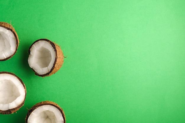 緑の無地の背景、抽象的な食品トロピカルコンセプト、トップビューコピースペースにココナッツフルーツ