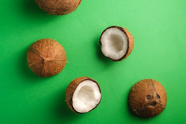 緑の無地の背景、抽象的な食品トロピカルコンセプト、トップビューでココナッツフルーツ