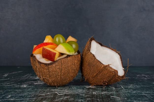 Noce di cocco piena di mele e uva sulla superficie in marmo