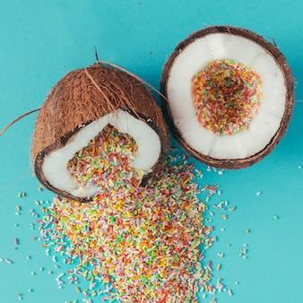 青い壁にカラフルなスプリンクラーがいっぱいのココナッツ。フラットレイ