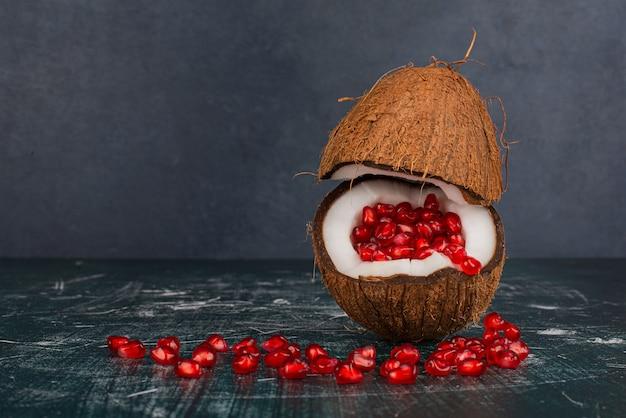 Noce di cocco piena di melograno sulla superficie in marmo