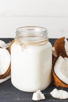 Coconut and  glass of coconut milk on  wooden surface