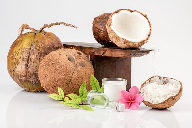 ココナッツおろし金、細かく刻んだココナッツ、ココナッツ全体、ココナッツの半分と白で隔離されたガラス瓶の中の油。