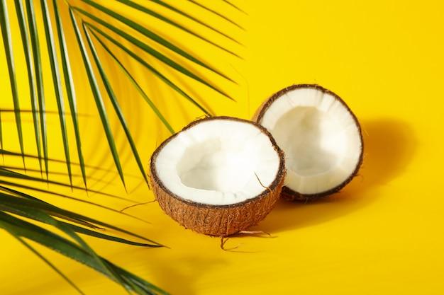 코코넛 반쪽과 노란색 팜 지점을 닫습니다