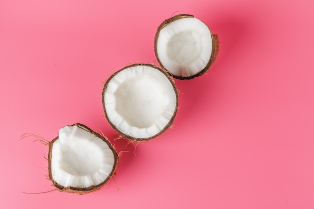 Coconut halves on a bright pink