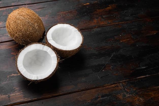 Половинки кокоса, набор кусочков кокоса, на фоне старого темного деревянного стола, с местом для текста