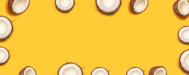 Coconut halves frame on a yellow background with space for text, flat lay.