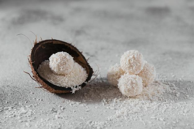 Кокосовые полезные шарики без сахара в кокосовой скорлупе с кокосовой стружкой на светло-сером белом фоне
