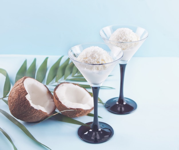 Coconut ice cream on the blue background with palm leaf and coconut