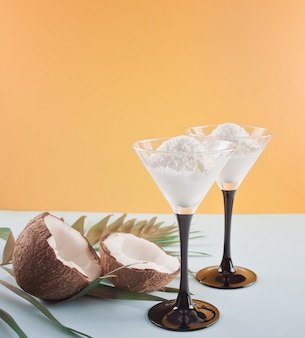 Coconut ice cream on the blue and orange background with palm leaf and coconut