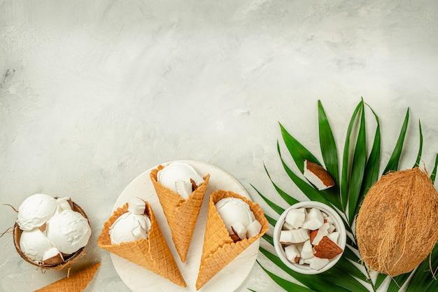 Конусы кокосового мороженого на конкретном сером фоне. вид сверху, копия пространства.