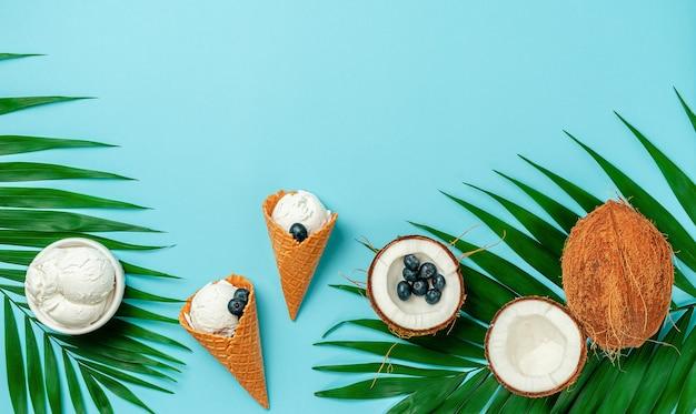 Конусы кокосового мороженого с черникой на бирюзовом фоне. вид сверху, копия пространства.