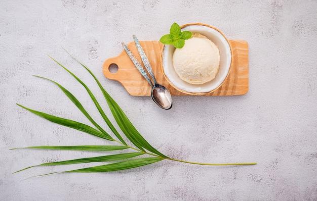 Ароматизаторы кокосового мороженого в половине кокосовой стружки на белом каменном фоне.