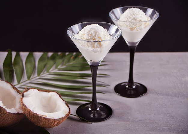 Coconut ice cream on the gray background with palm leaf and coconut