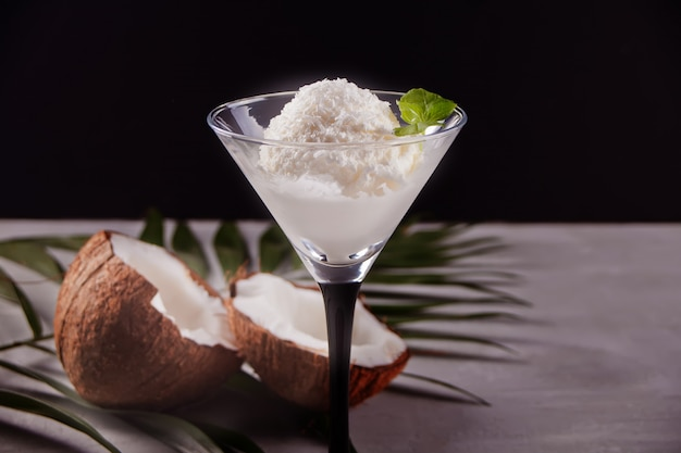 Coconut ice cream on the gray table with palm leaf and coconut
