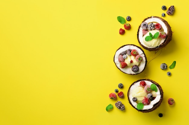 Coconut ice cream with fresh berries in coconuts halves