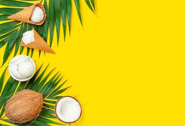Кокосовое мороженое с пальмовыми листьями на желтом фоне. вид сверху, копия пространства.
