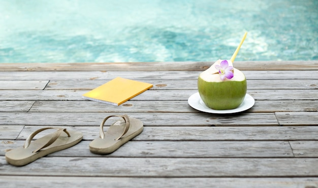 Coconut juice  with flower and book by the swimming