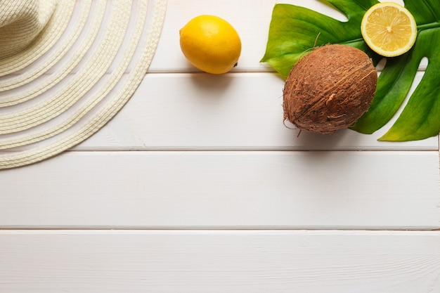 Coconut lemon monstera leaf and hat on a white wooden background with copy space