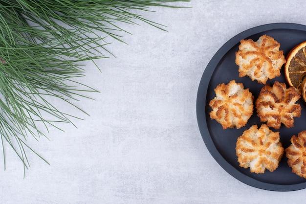 オレンジスライスとダークボード上のココナッツマカロン。高品質の写真