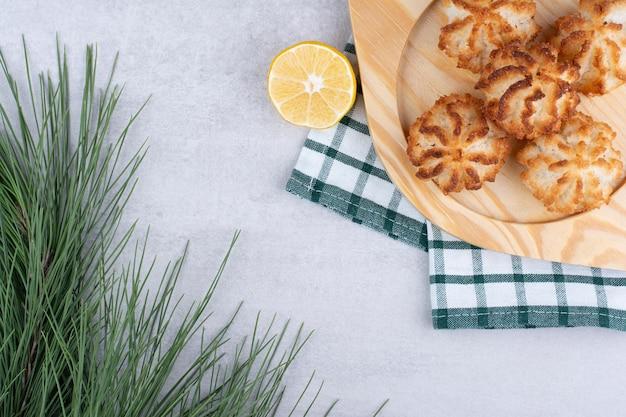 Кокосовое миндальное печенье на деревянной тарелке с разрезанным наполовину лимоном. фото высокого качества