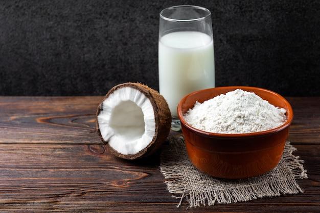 Кокосовое молоко и мука на темном деревянном фоне.