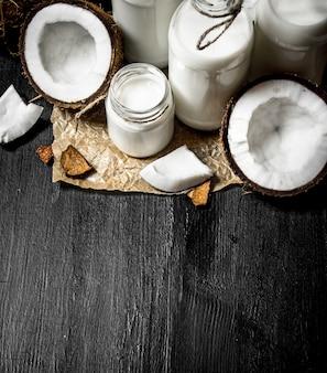 Coconut milk in bottles. on a black wooden background.