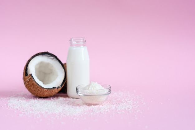Coconut milk in the glass bottle, coconut flakes and fresh coconut on pink background.