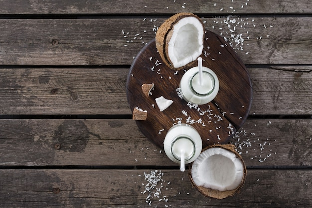 Coconut milk in glass bottle on wooden table. vegan non dairy healthy drink. healthy eating concept