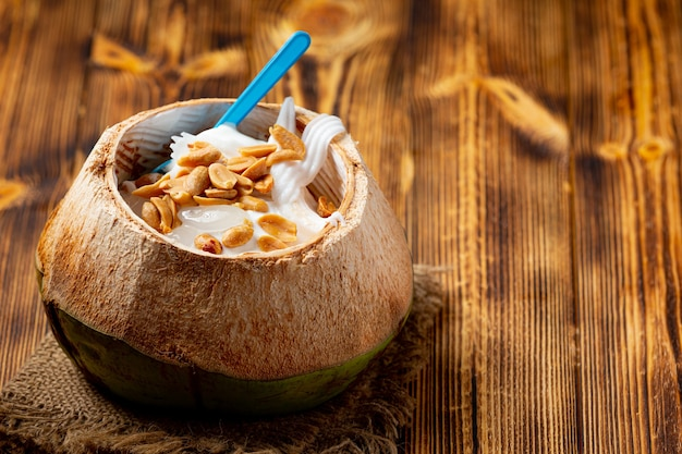 Coconut milk ice cream in the coconut shell on the dark wooden surface