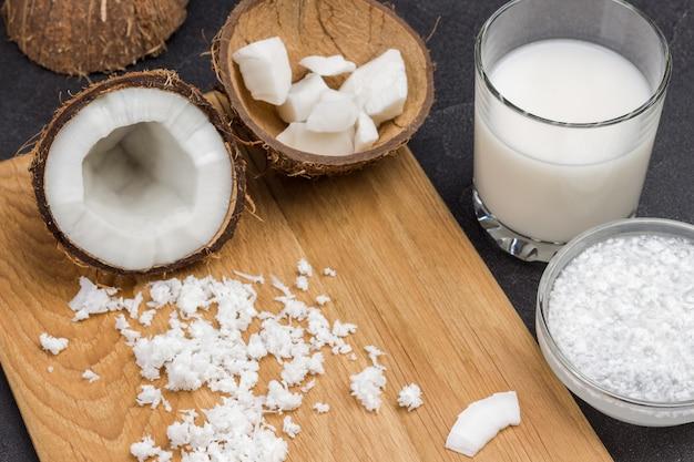 ガラスとボウルにココナッツミルク。ココナッツフレーク、半分新鮮なココナッツ、