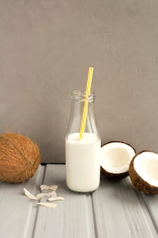 ガラス瓶のココナッツミルクと灰色の背景のココナッツ