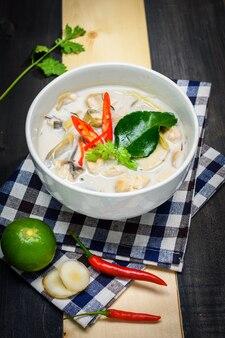 닭고기 또는 태국 치킨 코코넛 수프 (tom kha gai)가있는 코코넛 밀크 스프, 테이블 천, 테이블 탑 뷰, 태국 현지 음식