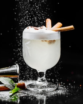 Coconut milky cocktail with foam and cinnamon sticks.