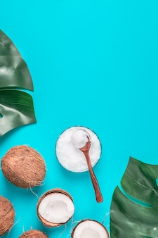 熱帯の葉の背景にココナッツオイルとココナッツ