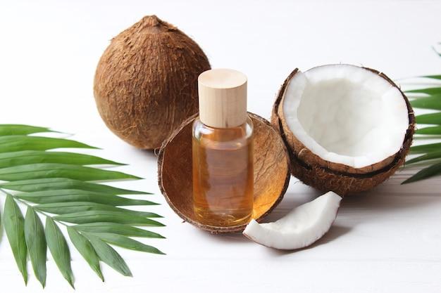 코코넛 오일과 코코넛 야자나무 가지를 닫습니다.