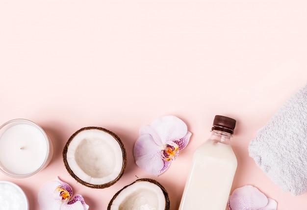 ココナッツオイルとピンクのテーブルに新鮮なココナッツの半分。ヘアケアスパのコンセプトです。