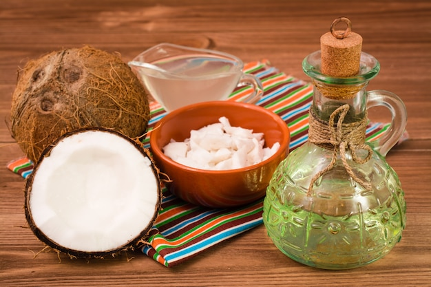 Coconut oil in a bottle, coconut milk and coconuts on a wooden table