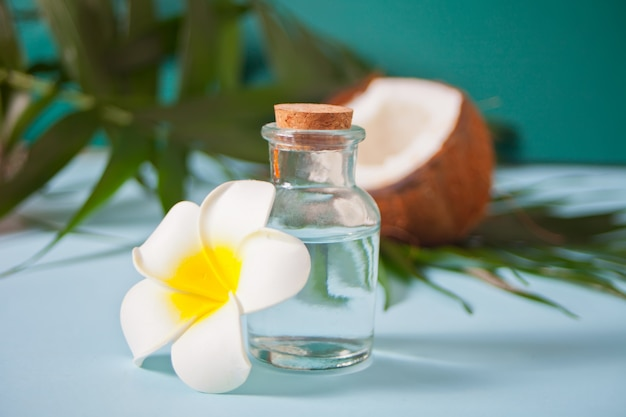 Coconut oil in a bottle with coconuts, flower plumeria frangipani and green palm tree leaf. healthy food, skin care concept.