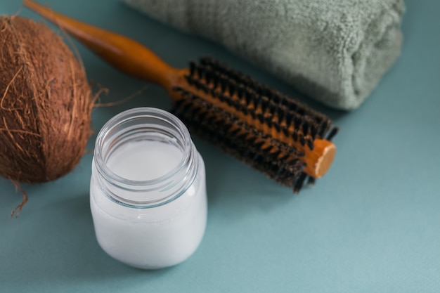 Coconut oil in a bottle with coconuts, towel and hairbrush on light blue surface