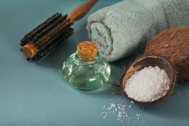Coconut oil in a bottle with coconuts, towel and hairbrush on light blue