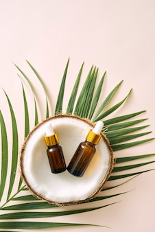 Coconut oil in bottle with open nuts and pulp in jar, green palm leaf background. natural cosmetic products.