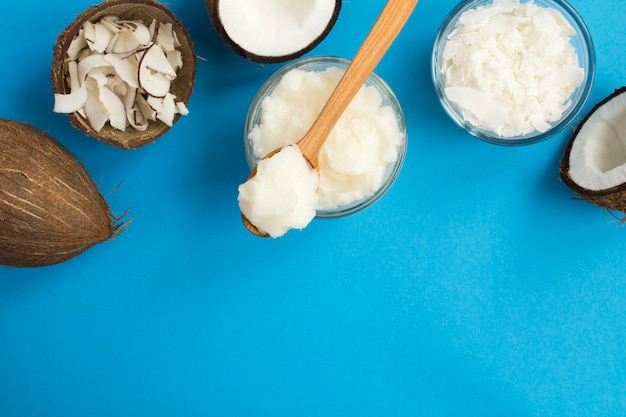 Coconut oil, coconut crisps and coconut flakes on the blue table. natural products. top view. copy space.