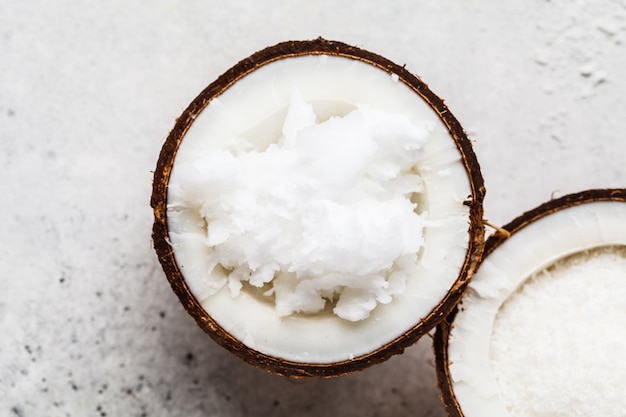 Coconut oil in a coconut shell on gray background, top view.